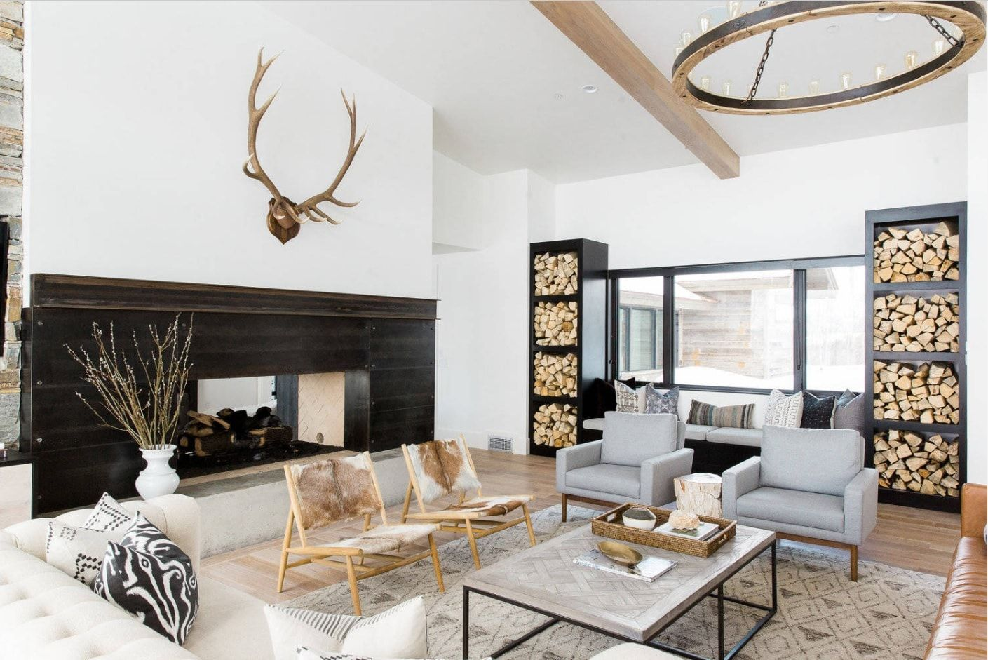 White loft styled interior with black fireplace and antlers above it