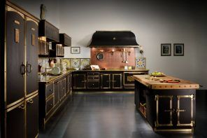 Dark kitchen design with golden fittings and ornament on facades