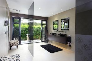 Unique white decorated ultramodern bathroom interior with spectacular idea of black glass partitions