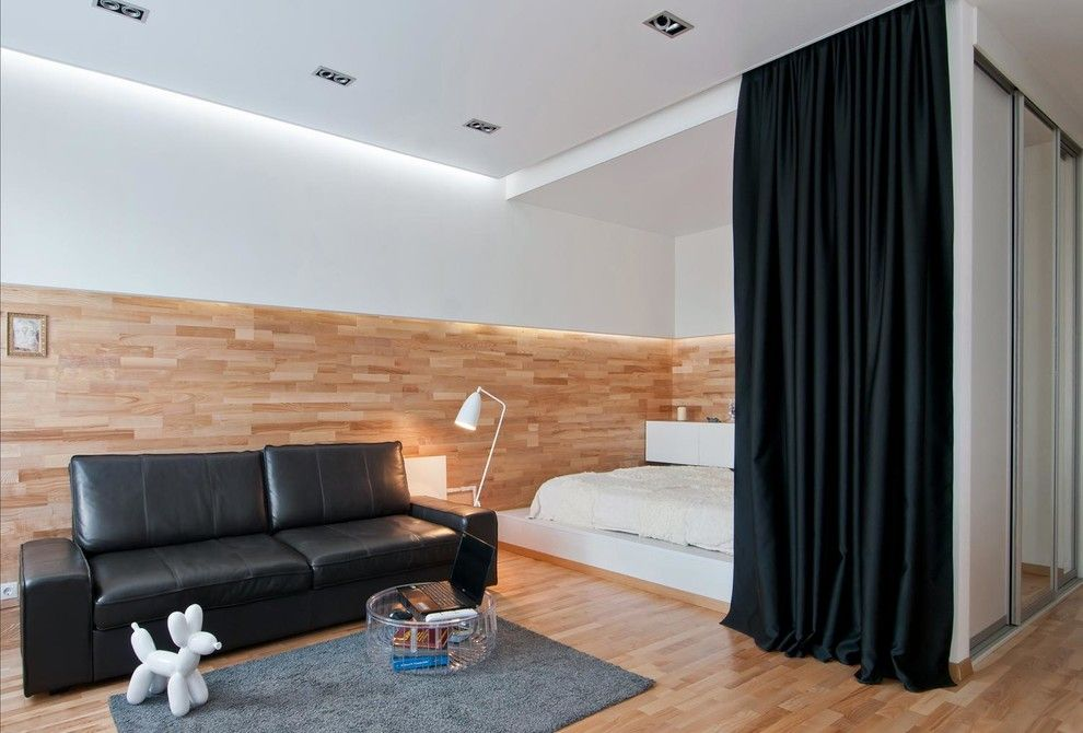 Two level decoration of wooden planks and white wall paint in the modern designed room with black furniture