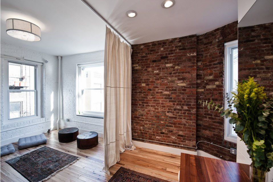 Loft space and brickwork accent wall divided by lightweigth tulle