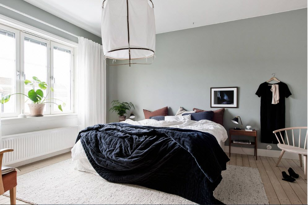 Black coverlet in the simple styled bedroom with olive painted walls