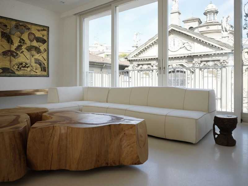 Unique table design of wood with white upholstered sofa in the neutral colored living