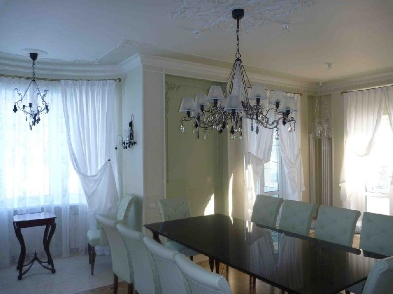 Gorgeous chandelier to emphasize the scale of interior шт the dining room with tulle on the windows