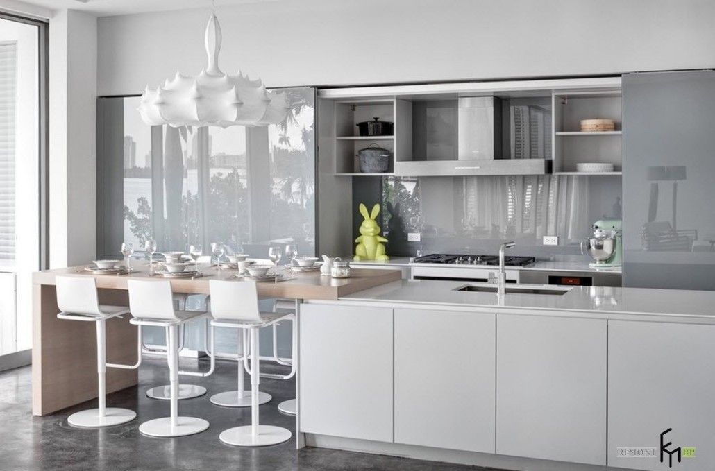 Pendant white lamp over the dining zone of modern kitchen