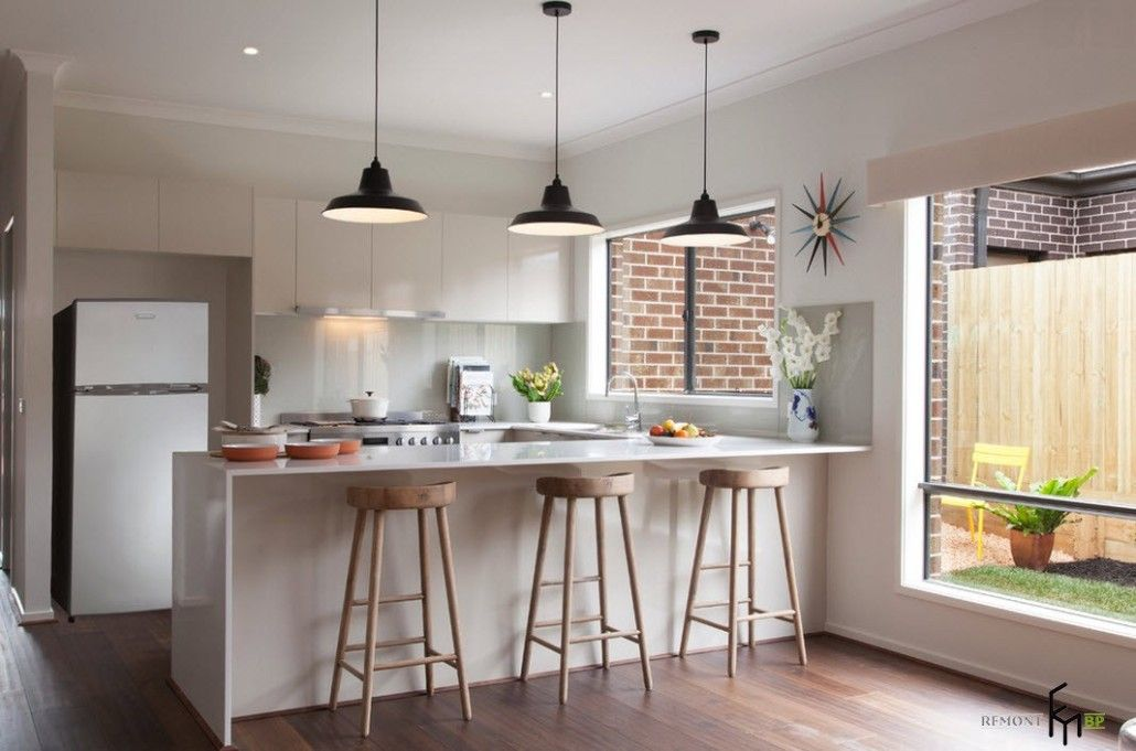 high wooden stools at the white glossy topped kitchen island highlighted by black lamps