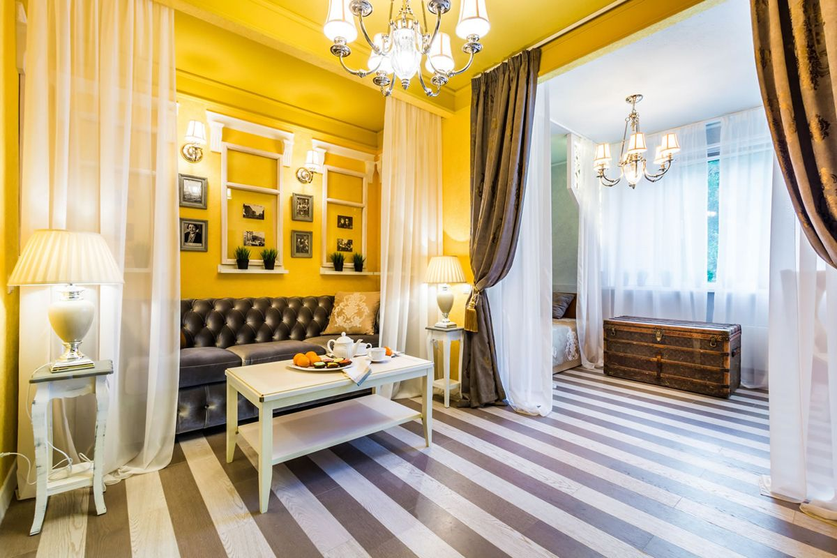 Yellow wall paint and striped flooring for the Classic designed open layout of the large living room