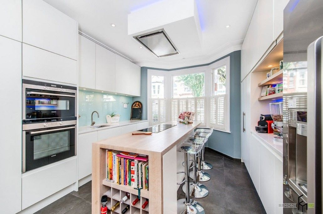 Unusual top light illuminator over the wooden kitchen island with open storage for books