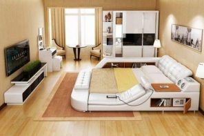 Modern bedroom interior with laminated floor and light brown wall finishing