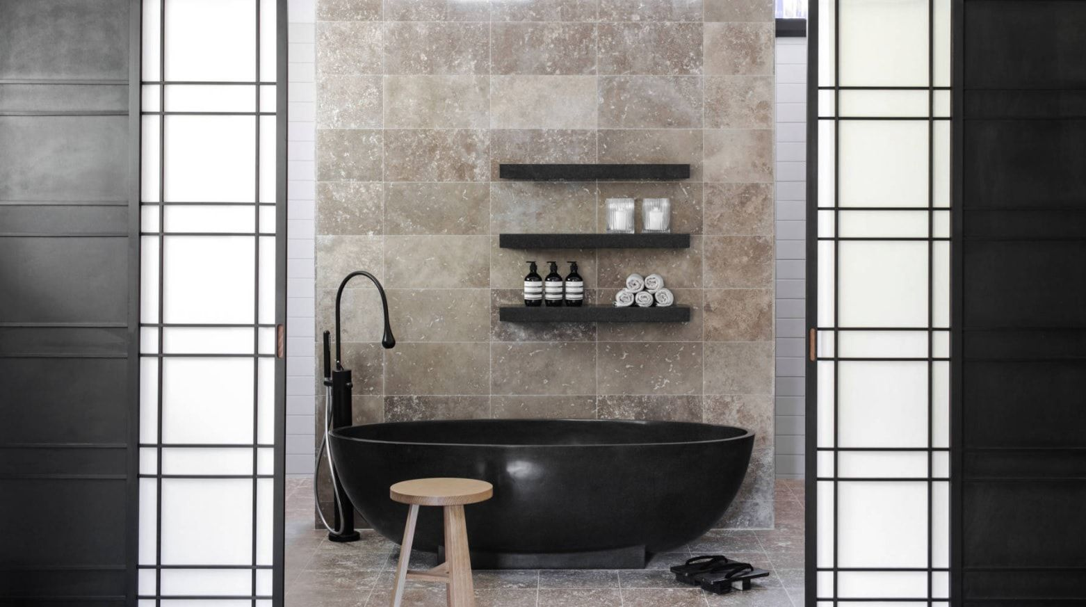 Contemporary Oriental styled black bathtub with tap and top shelves for gray marble trimmed room