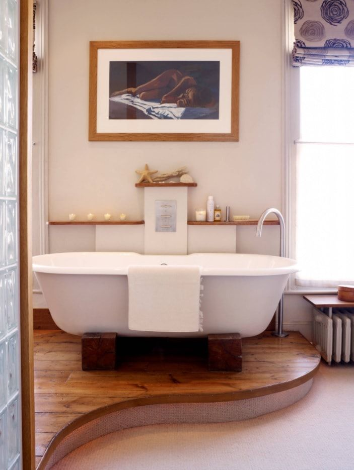 Classic styled bathroom with wooden imitating floor and central bathtub on pedestal