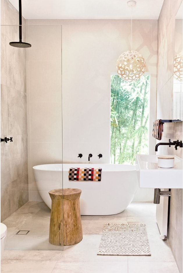 Minimalistic atmosphere in the bathroom with the window and white oval stone bathtub and black tap