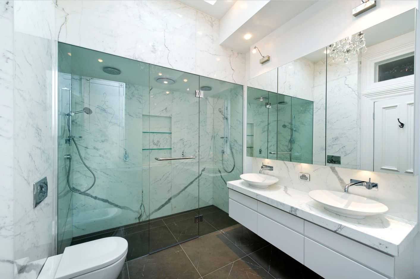 Amazing example of the main bathroom with large mirrors and glass partition of the shower zone