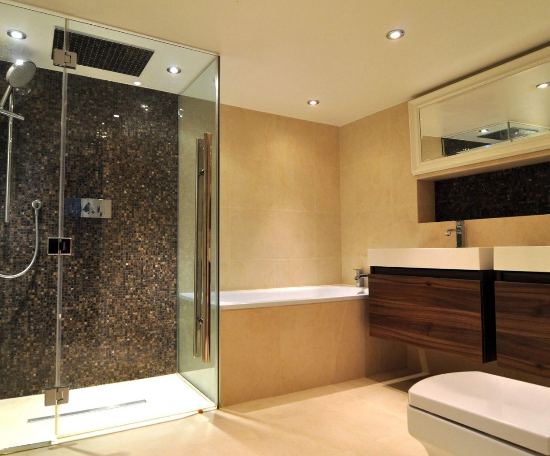 Shining Modernity in the light brown decorated bathroom with glass shower cabin trimmed with pebbles