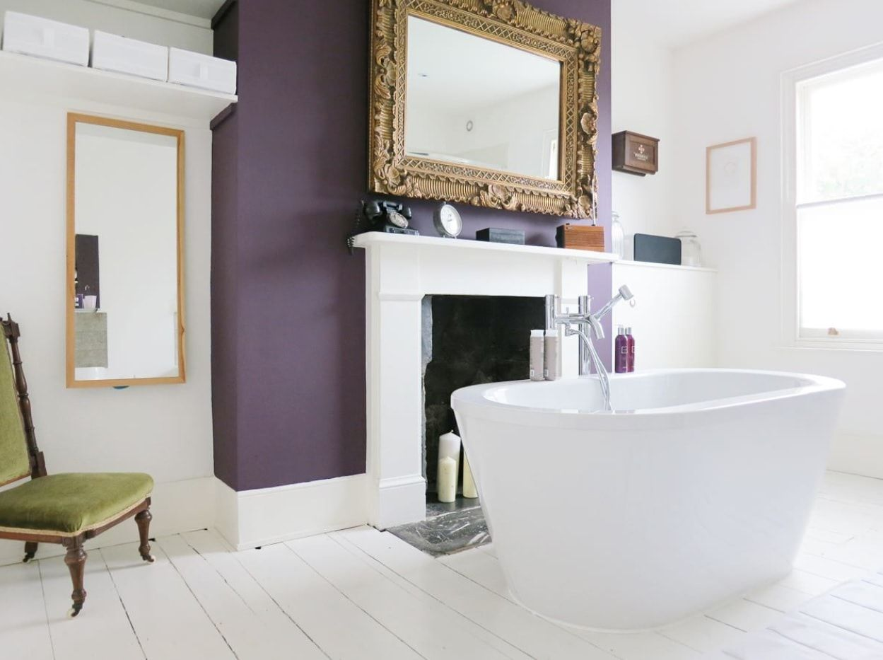 Unusual vintage styled bathroom with purple accent wall and large mirror in picture frame