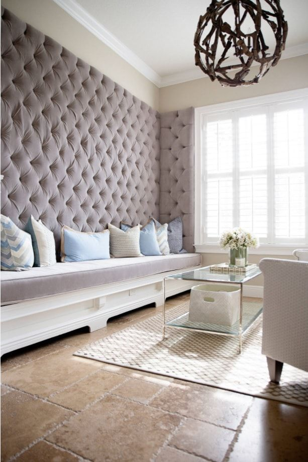 Quilted gray wall and the long sofa is unexpected design solution