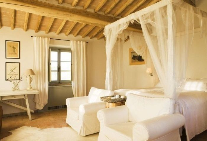 Tender cute bedroom design with rough treated wooden ceiling beams as the carcass for canopy