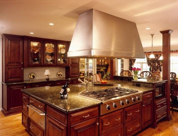 Red wooden noble fitted kitchen with the kitchen island and domed extractor hood of steel above it