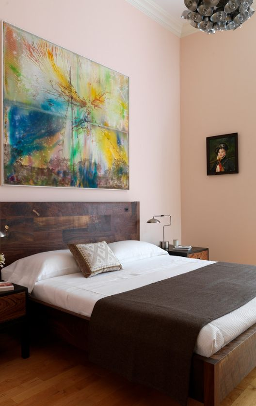 Large colorful panel above the raw wooden headboard