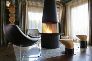 Chic natural fireplace with hood and leather armchair in the dark living room