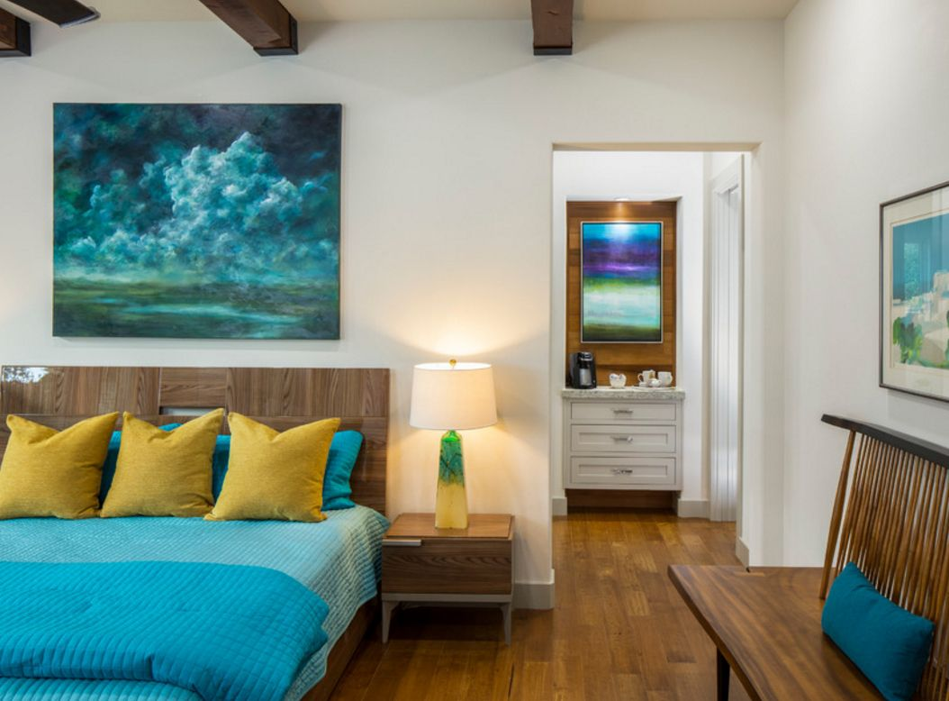 Open ceiling beams in the creatively designed bedroom with turquoise bed linen