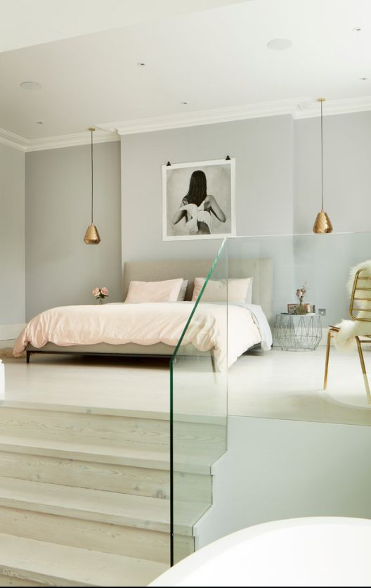 Glass partitions and the bed on the pedestal in the light colored master bedroom