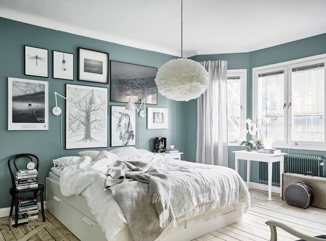 Turquoise calming bedroom design with plenty of different sized pictures