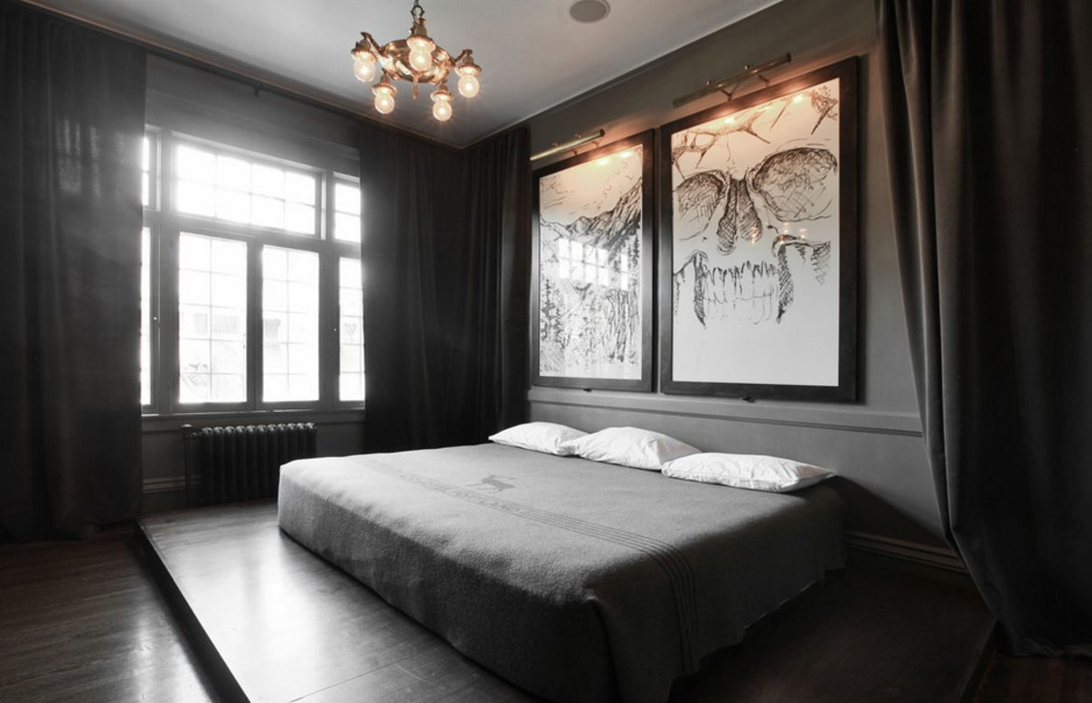Gloomy bedroom design with platform bed and scary sketches on the headboard wall