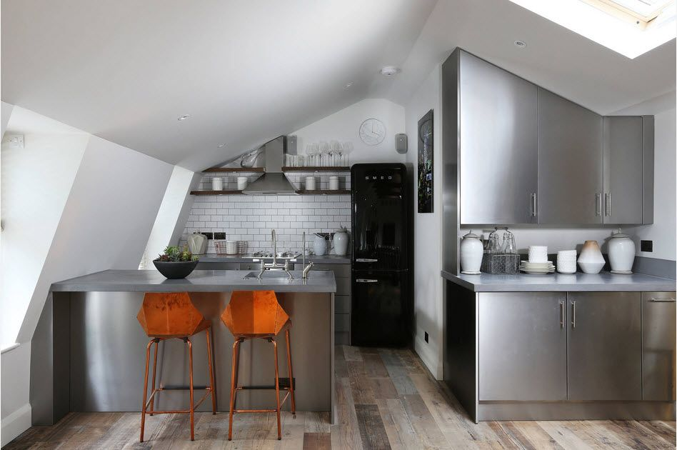 Steel surfaces at the hi-tech kitchen with orange bat stools