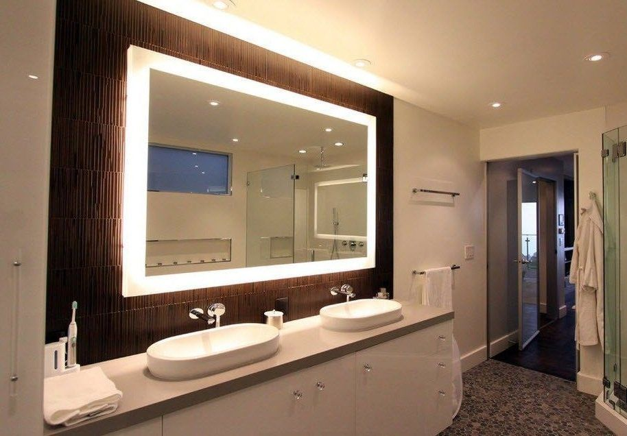 Grand wooden framed mirror in the modern decorated bathroom