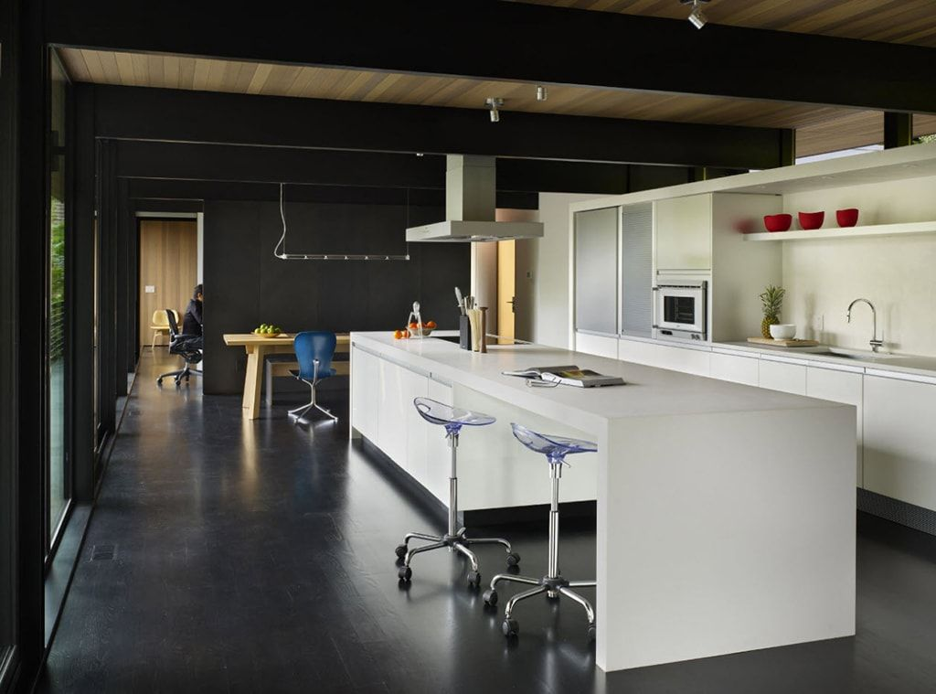 Open layout apartment with dark floor and white kitchen furniture