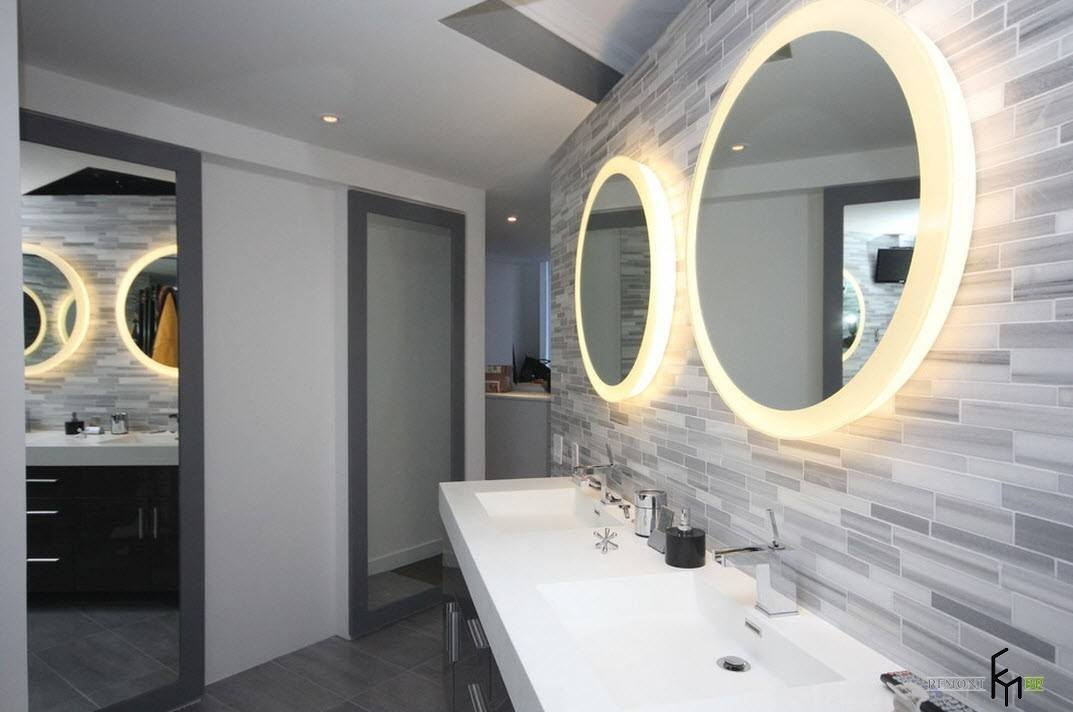 Round LED-lighted mirror and stone trimmed walls in the bathroom
