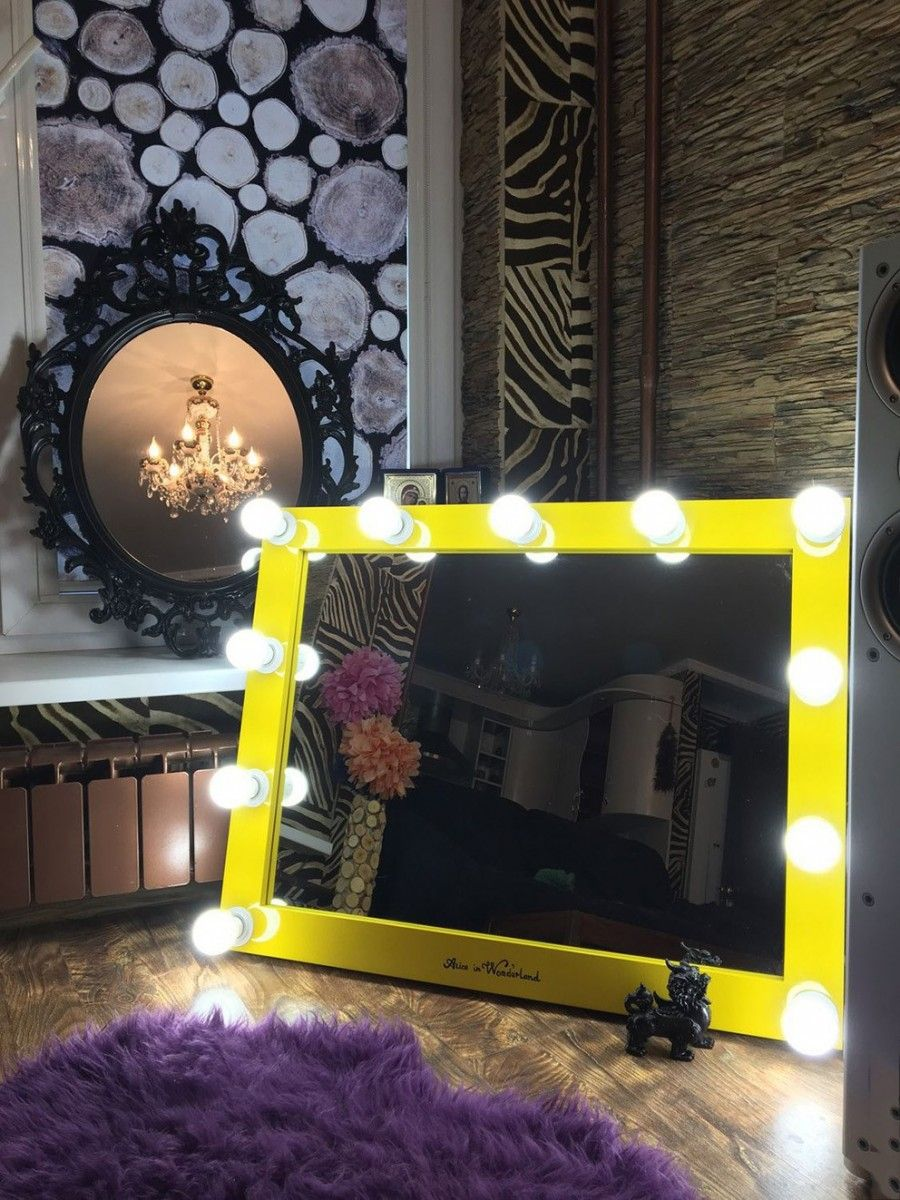 Yellow framed mirror with bulbs on the perimeter