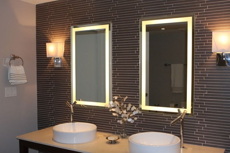 Ultramodern bathroom design with round sinks and LED backlight of the mirrors