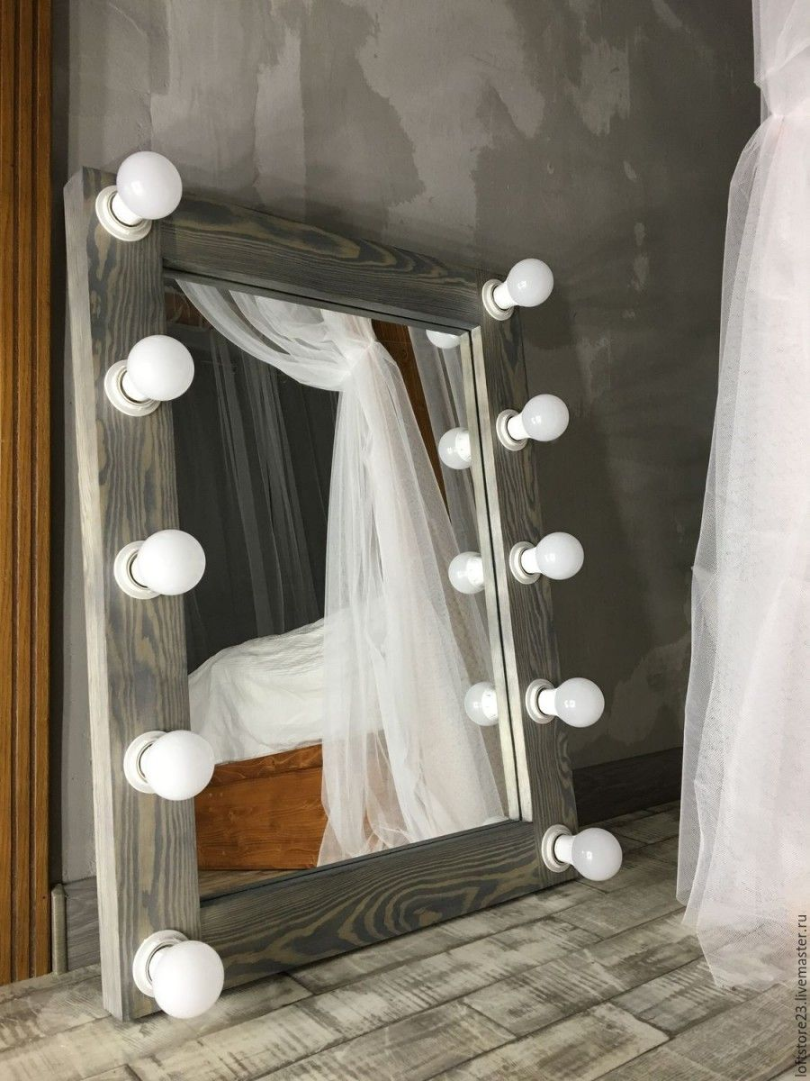 Small peculiar wooden framed mirror with bulbs for lighting