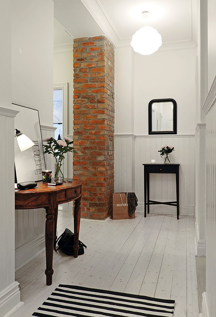 Brickwork column and wooden table in the white classic entry