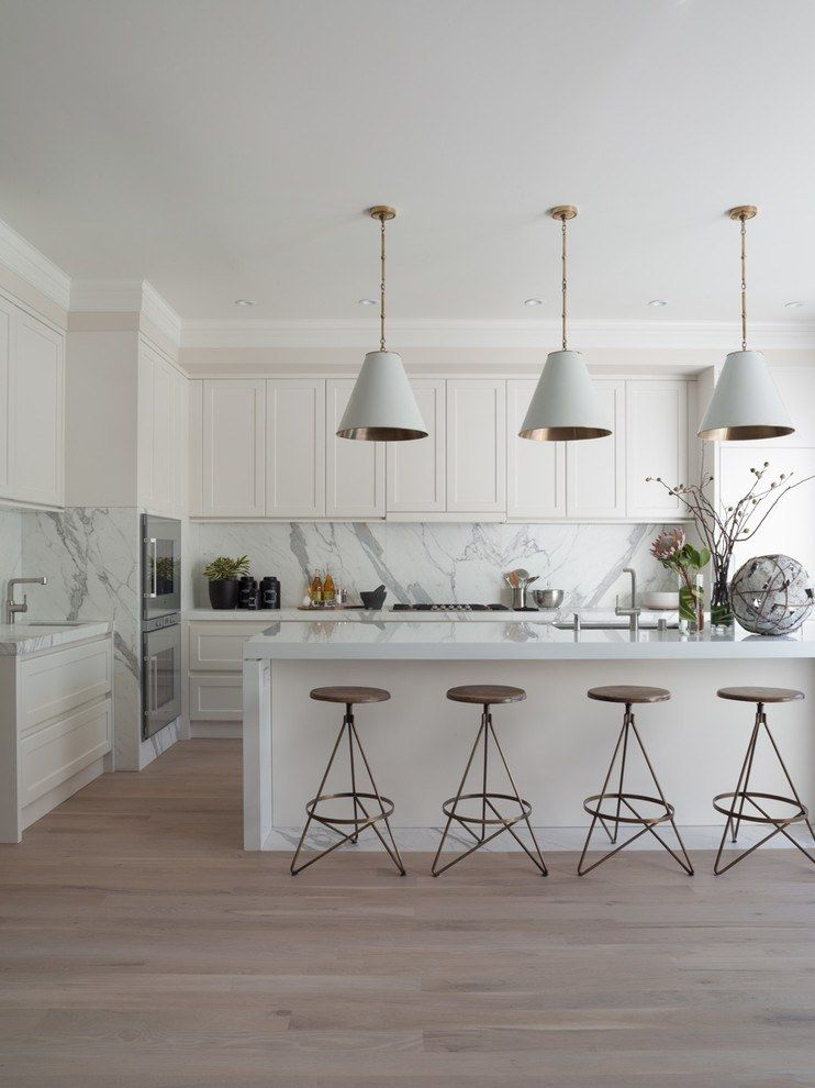 Light facades of the furniture and marble splashback at the large modern kitchen
