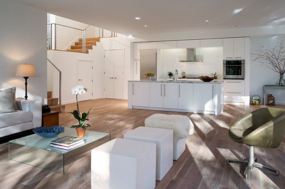 White wooden furniture in the kitchen and living zones of the open layout apartment