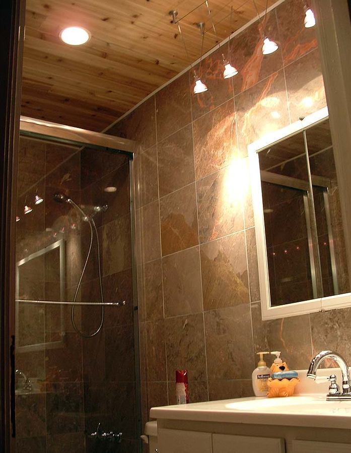 Bathroom with stone tiled walls and LED lighted mirror