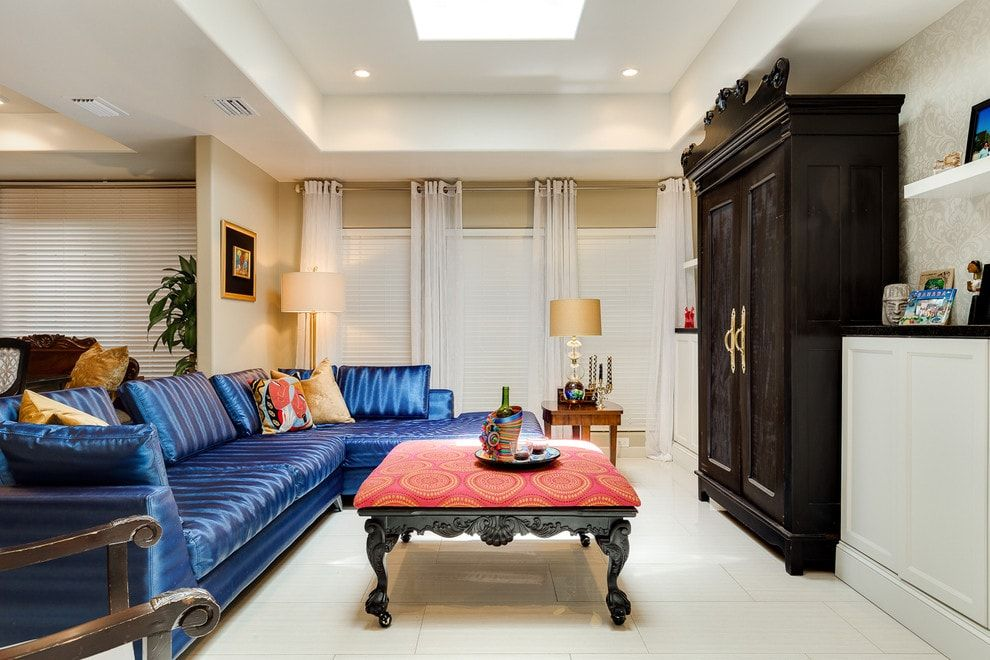 Dark wooden furniture in the Classic designed living room with blue sofa and carved coffee table
