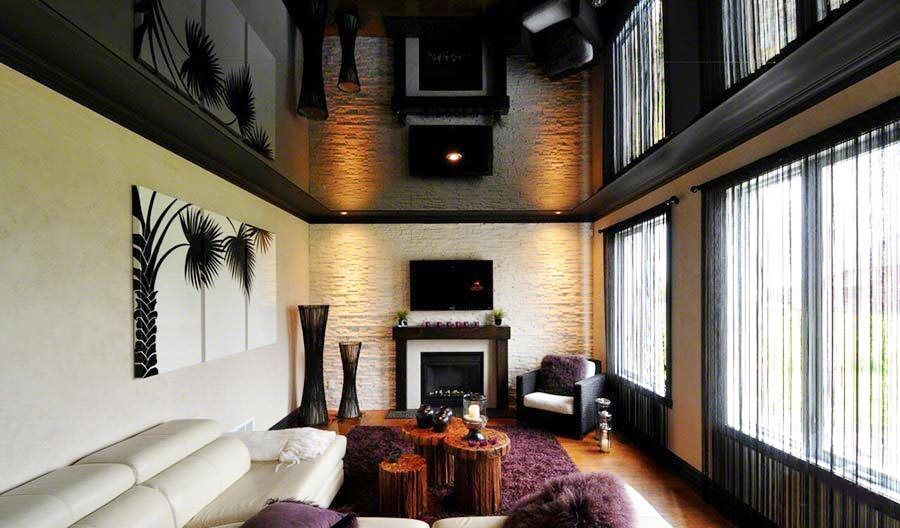 African touch in the living room with artificial fireplace and black tension ceiling
