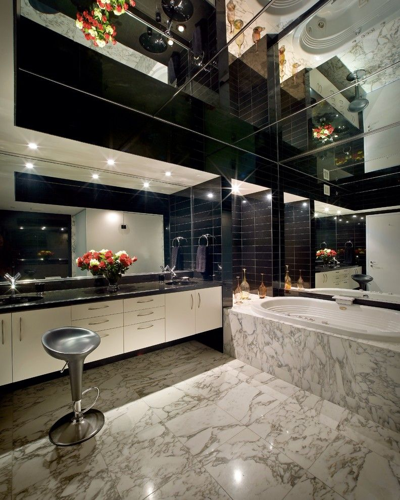 Modern bathroom design with large mirror and mirror tiles at the ceiling