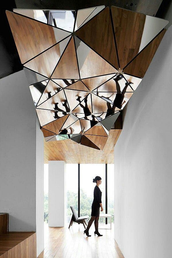 Complex designed mirror ceiling in the light colored corridor