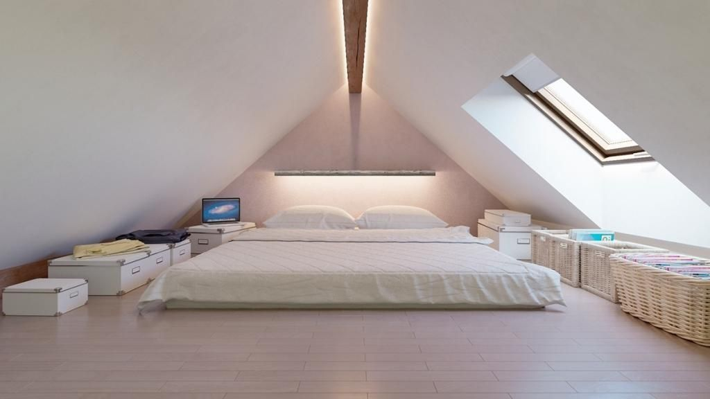 Loft designed white bedroom with huge bed in the center