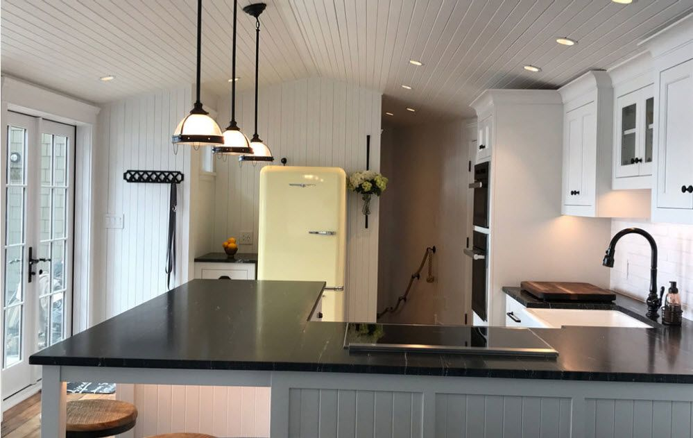 Modern design of the large open layout apartment with the retro designed fridge at the kitchen zone