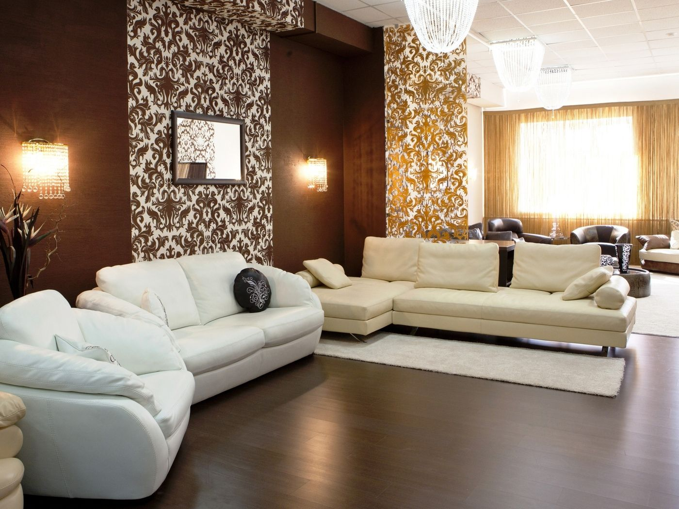 Dark pattern of the wallpaper and white leather sofas for living
