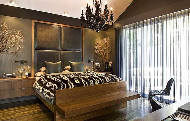 Quilted headboard of leather and Gothic dark chandelier in the bedroom