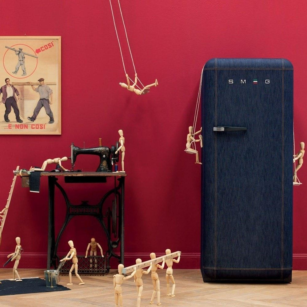 Unusual red textured wallpaper and jeans blue refrigerator
