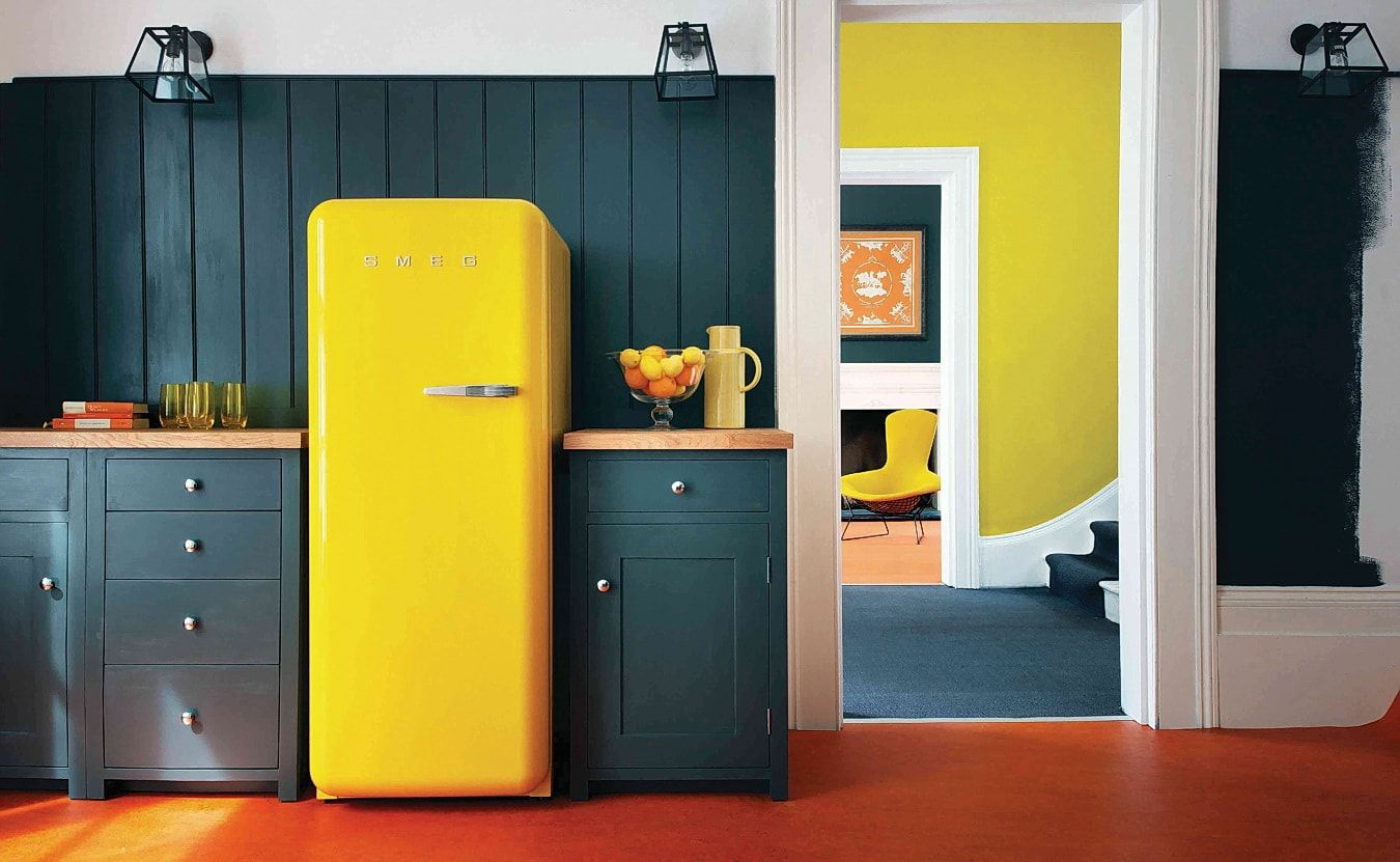 Yellow facaded fridge and dark furniture, and splashback for Casual styled kitchen