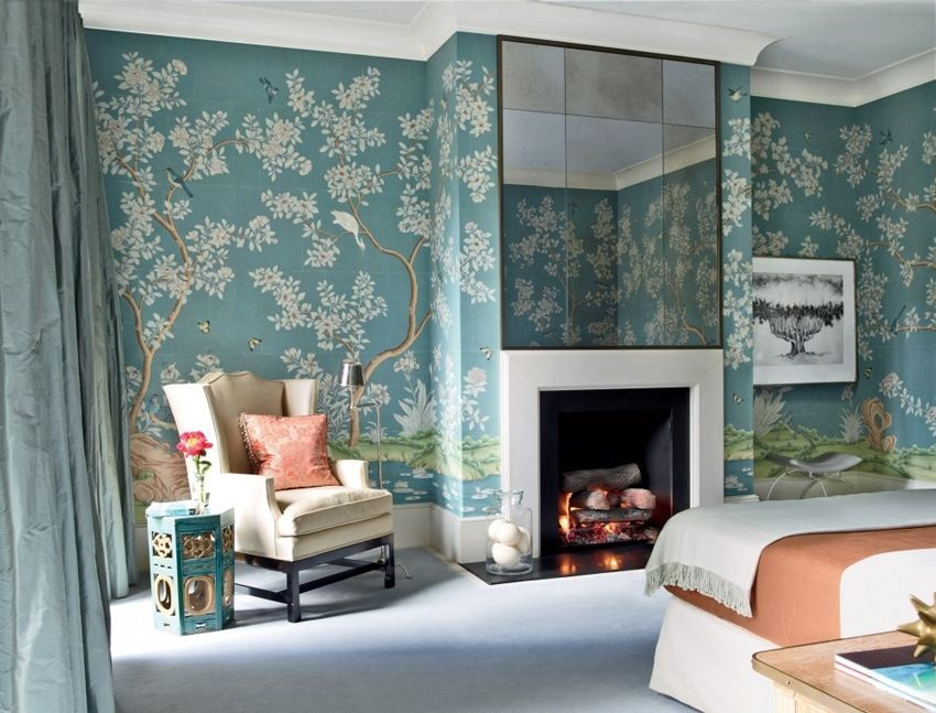 Unusual floral theme in blue hues of the wallpaper in living room and large mirror over the fireplace